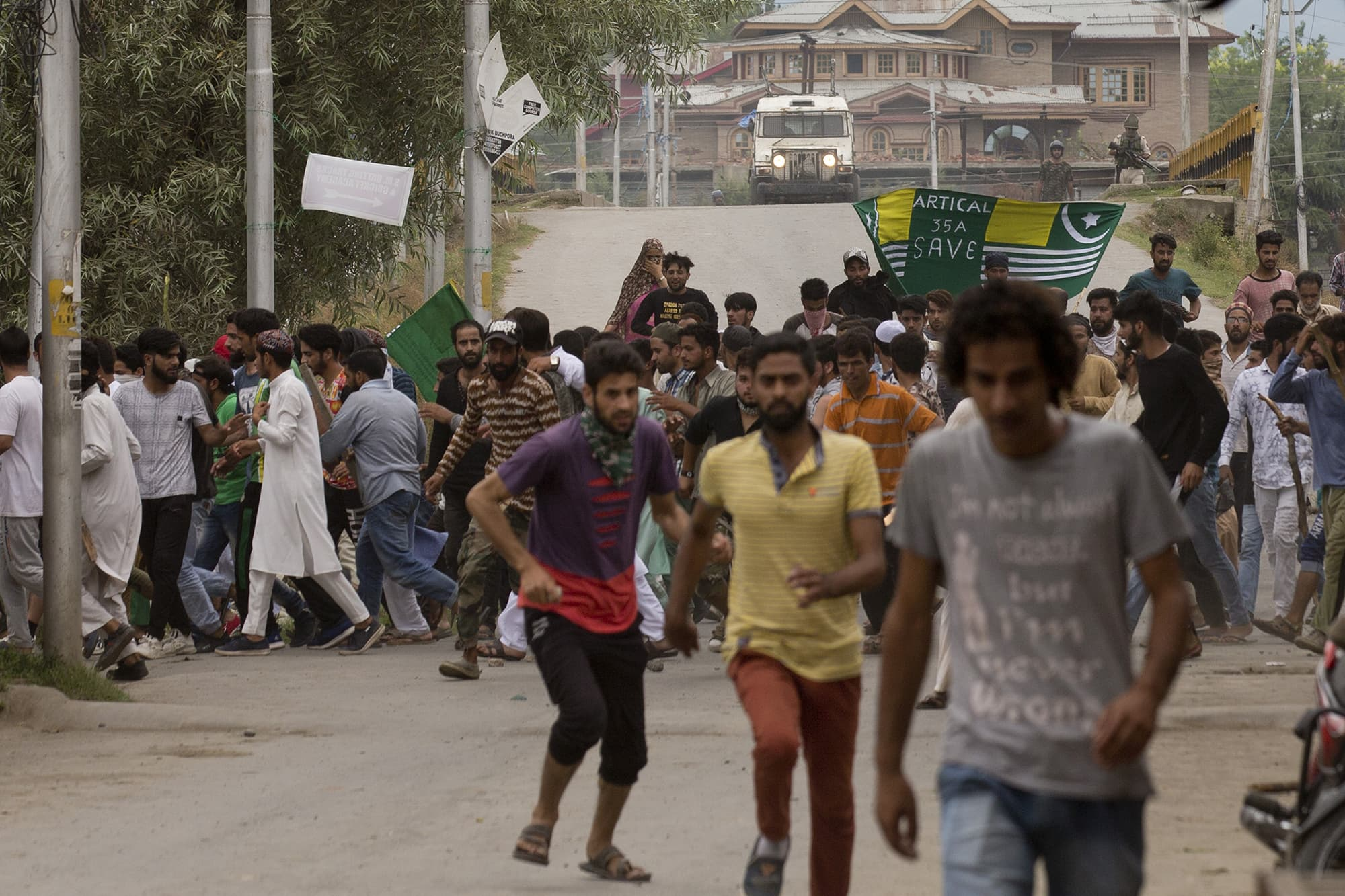 Kashmiris run for cover as Indian policemen chase them during a protest march in Srinagar. ─ AP
