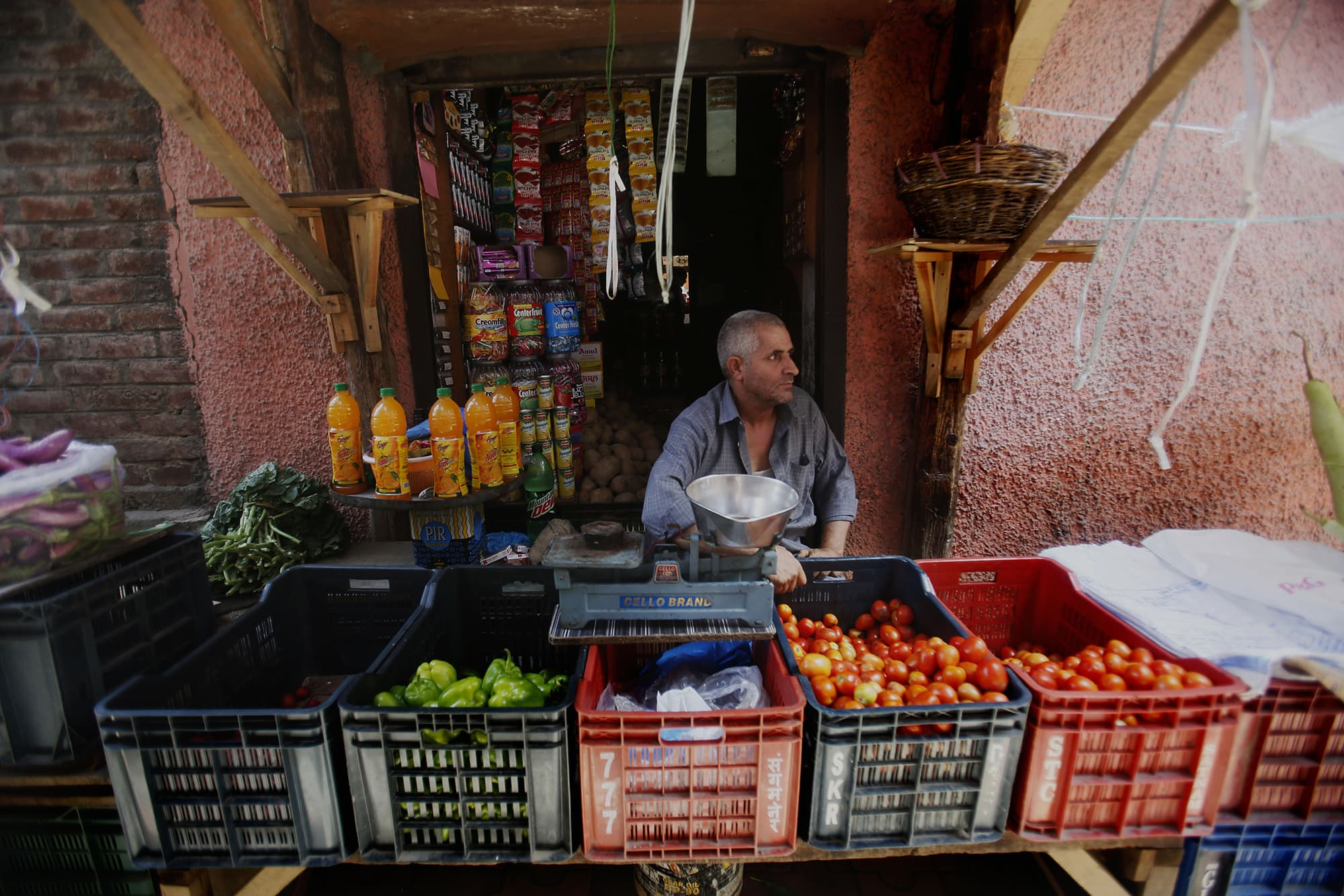 A Kashmiri waits for customers at his temporary shop during curfew in Srinagar. ─ AP