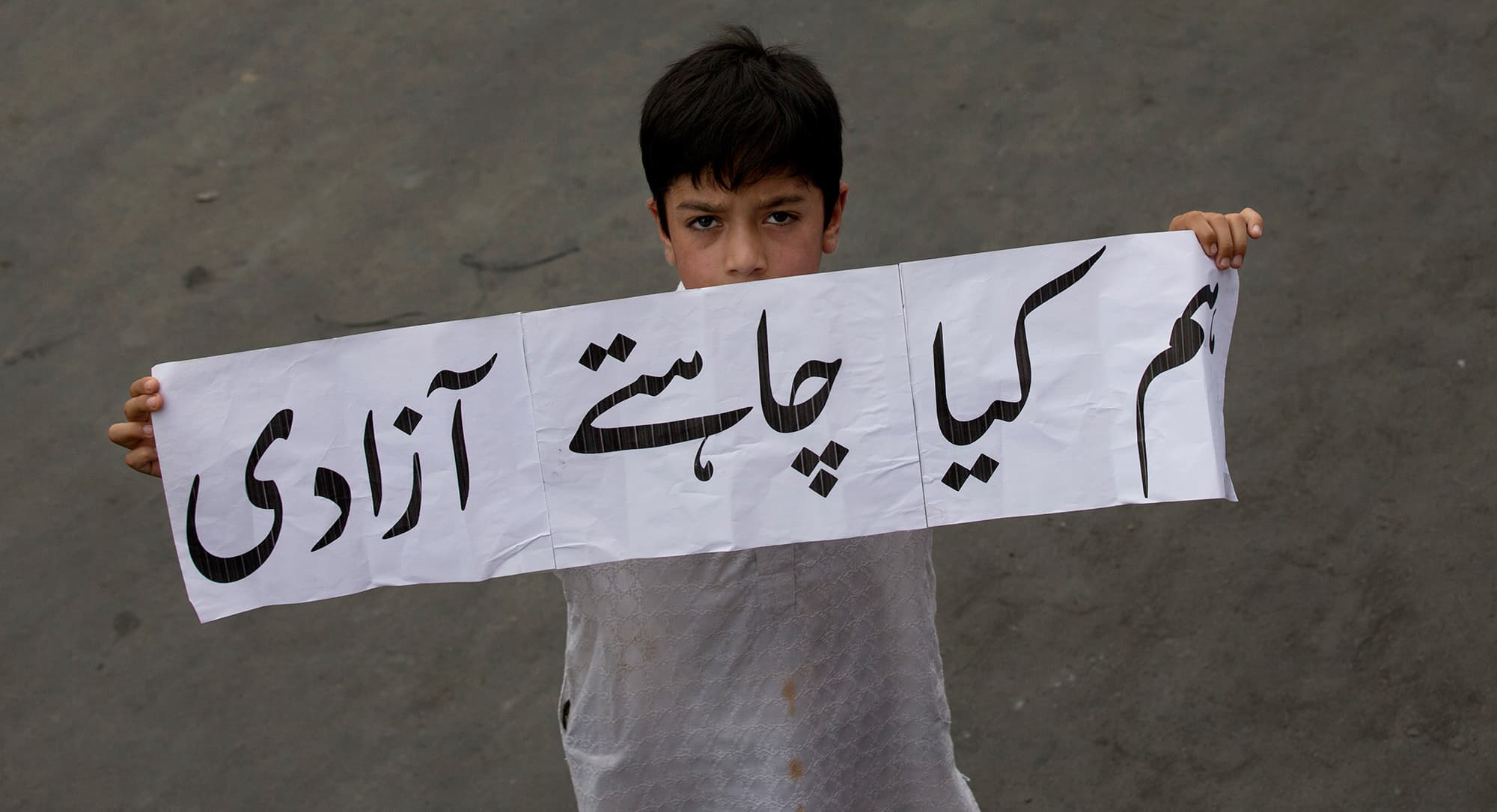 "In this Friday, Aug. 9, 2019, photo, a Kashmiri boy holds a banner that reads ""What do we want- Freedom,"" and participates in a protest march in Srinagar, Indian controlled Kashmir. Authorities enforcing a strict curfew in Indian-administered Kashmir will bring in trucks of essential supplies for an Islamic festival next week, as the divided Himalayan region remained in a lockdown following India's decision to strip it of its constitutional autonomy. The indefinite 24-hour curfew was briefly eased on Friday for wee"