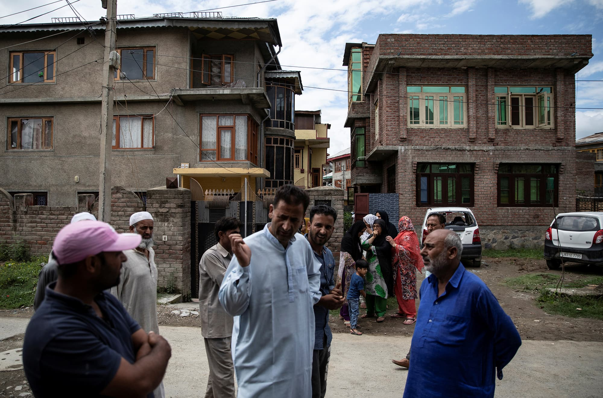 Kashmiri residents stand in a street in a neighbourhood where dozens of houses and vehicles were allegedly damaged by Indian security forces after clashes between protesters and the security forces in Srinagar under curfew. ─ Reuters