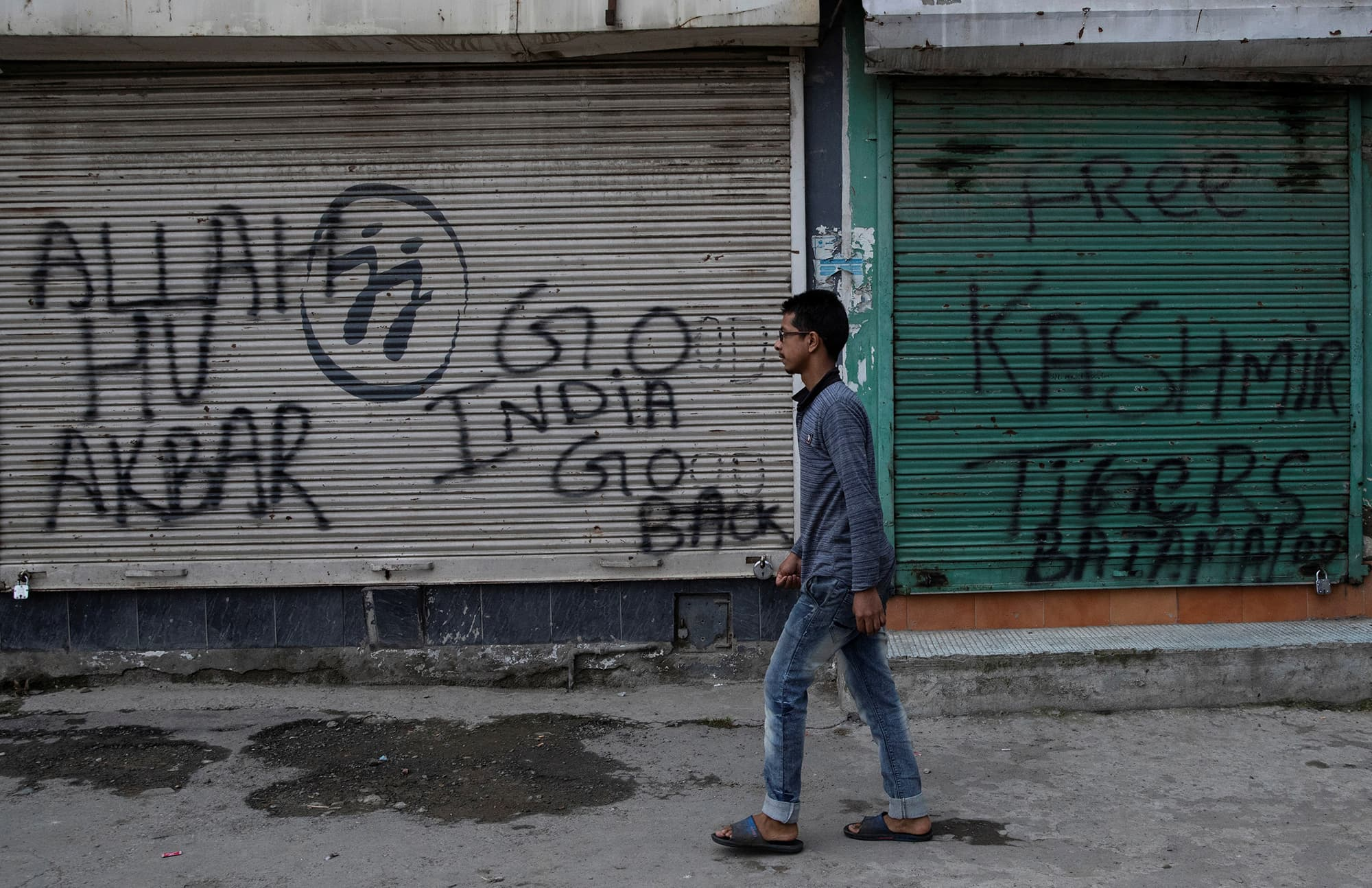 A Kashmiri boy walks past graffitied shutters of shops closed down during curfew in Srinagar. ─ Reuters