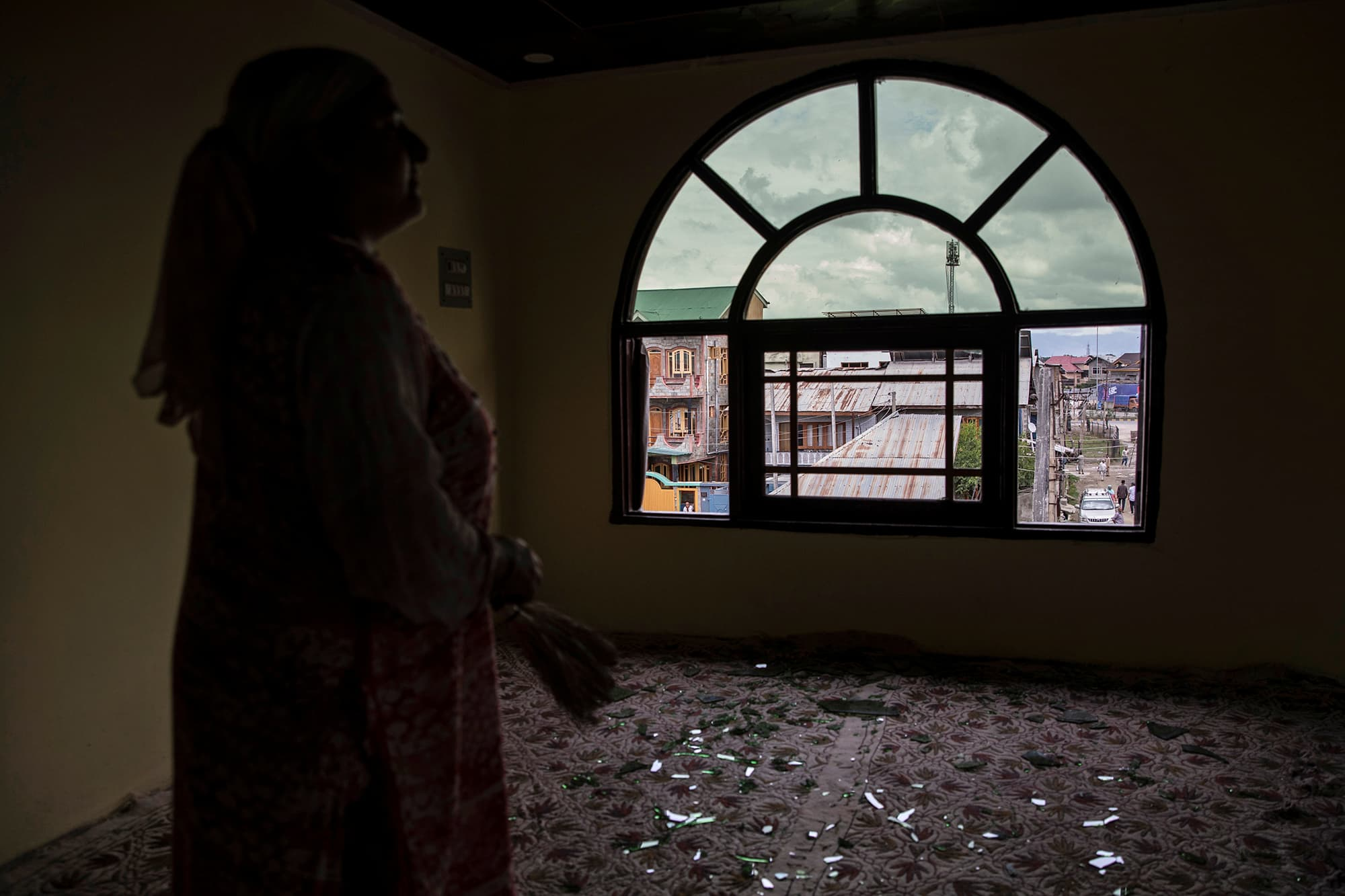 A woman stands next to a broken window of her house that was allegedly damaged by Indian security personnel after clashes between protesters and security forces during curfew in Srinagar. ─ Reuters