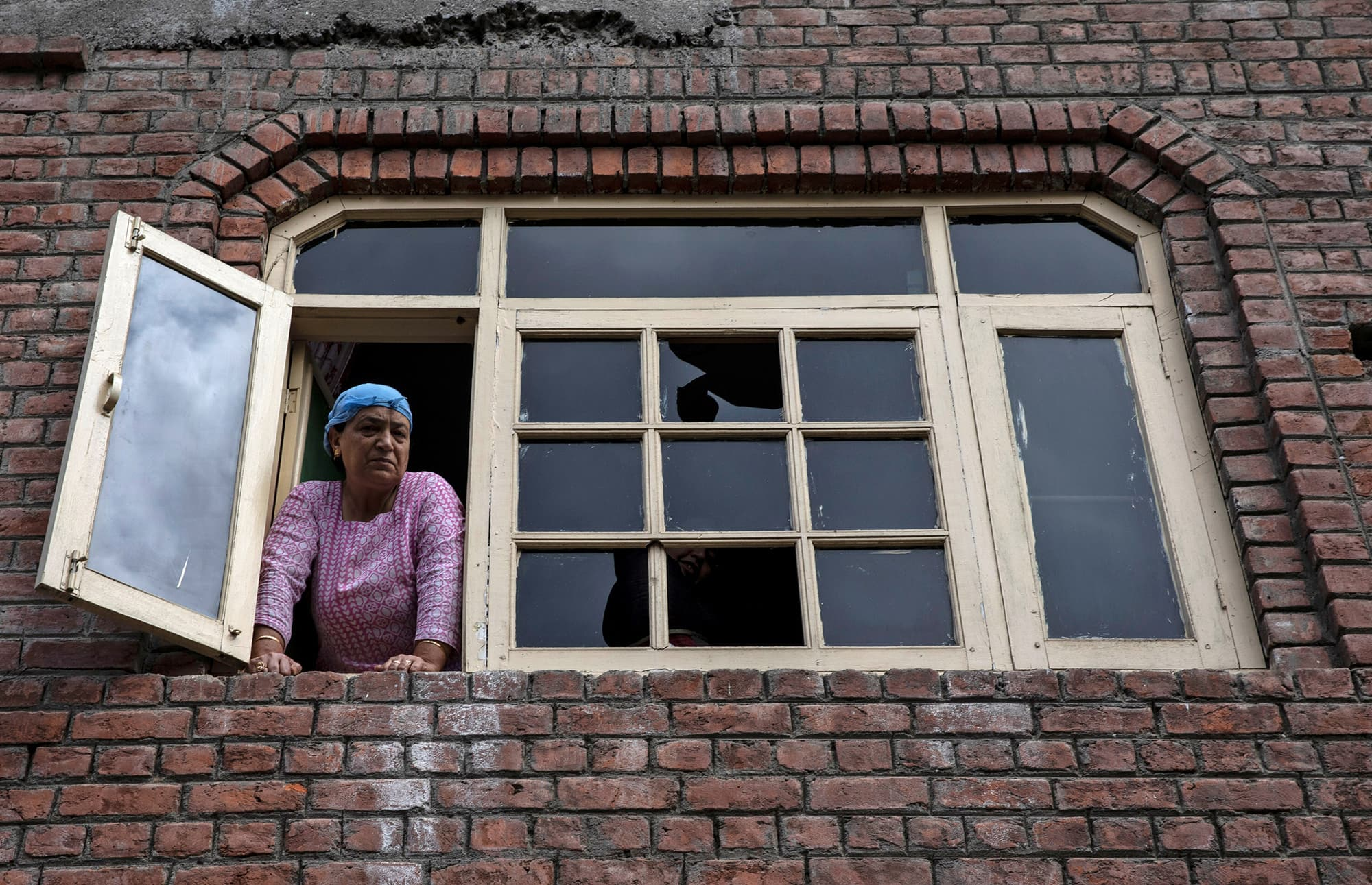 A Kashmiri woman looks out from a window of her house which was allegedly damaged by Indian security after clashes between protesters and the security forces during curfew in Srinagar. ─ Reuters