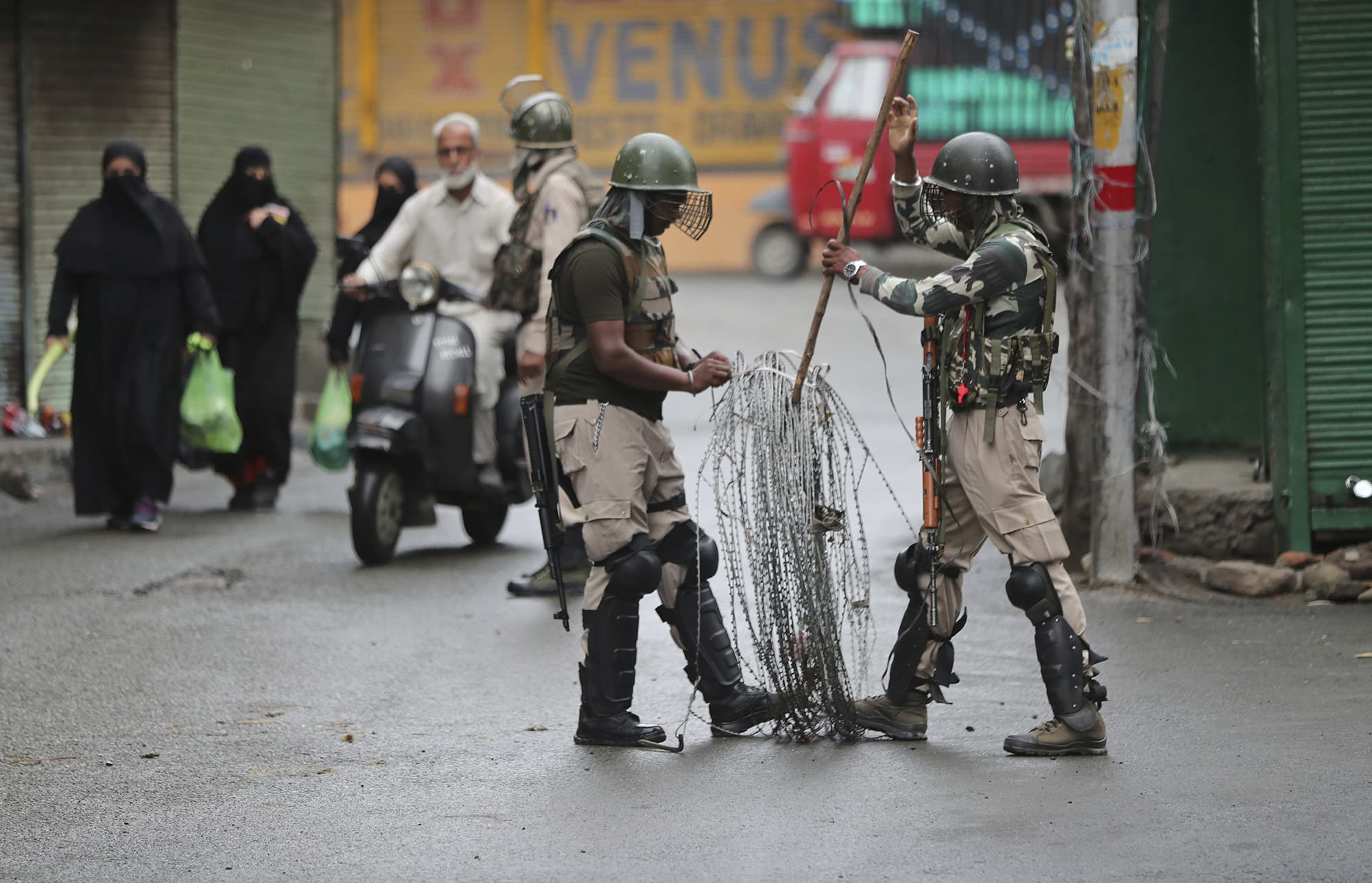 Indian paramilitary soldiers prepare to close off a street with barbed wire in Srinagar. ─ AP