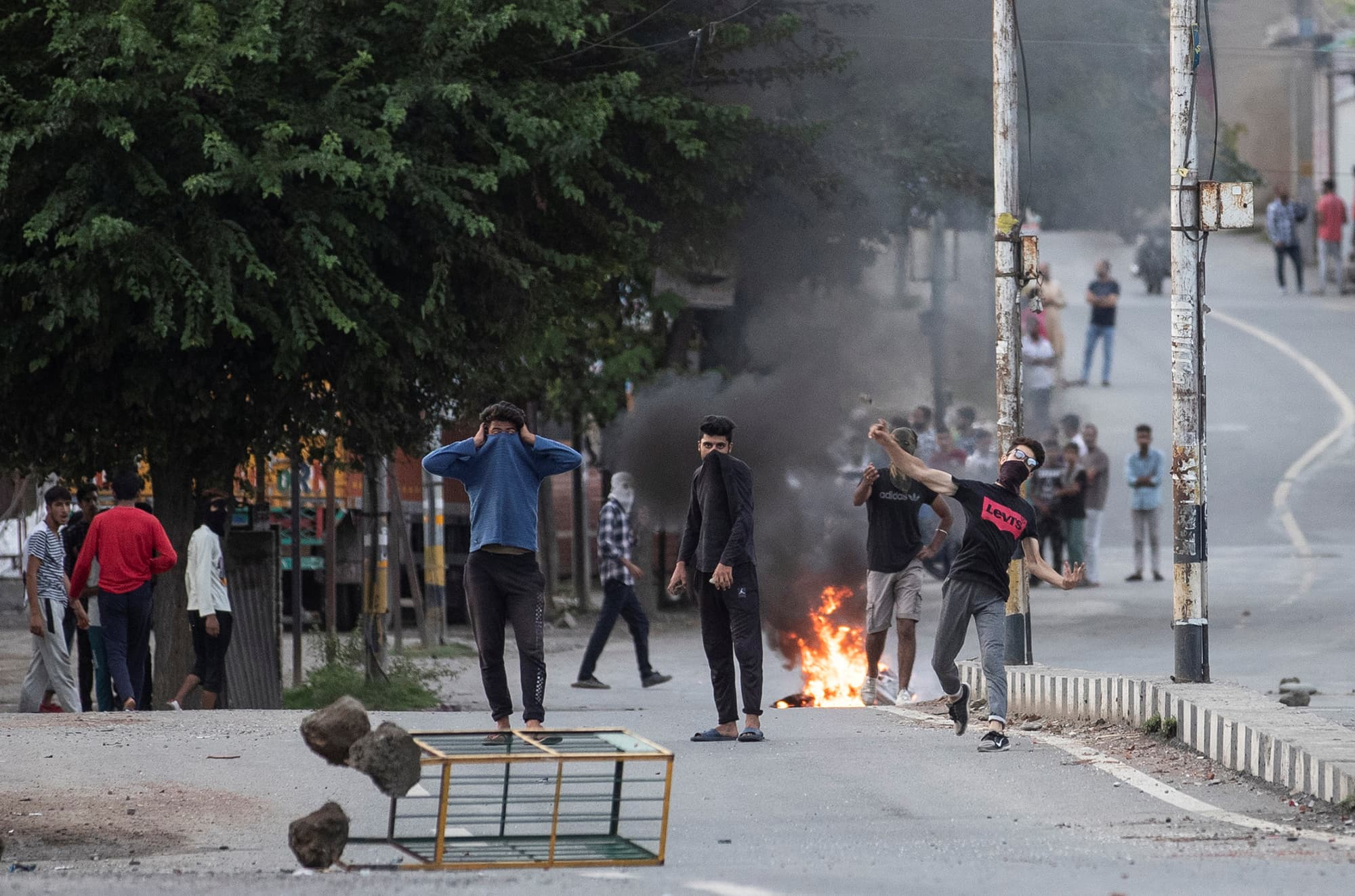 Kashmiri residents throw stones at Indian security personnel during curfew in Srinagar. ─ Reuters