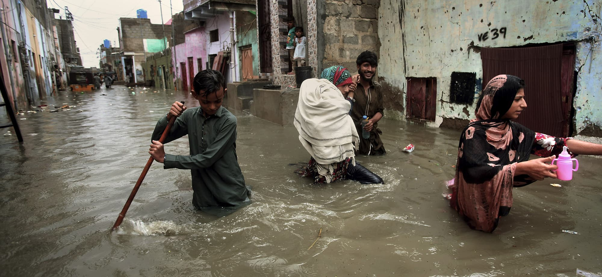 A family wades through a flooded street caused by heavy monsoon rains, in Karachi, Pakistan, Sunday, Aug. 11, 2019. Monsoon rains have inundated much of Pakistan, leaving large parts of the southern city of Karachi underwater and causing some deaths. (AP Photo/Fareed Khan) — Copyright 2019 The Associated Press. All rights reserved.