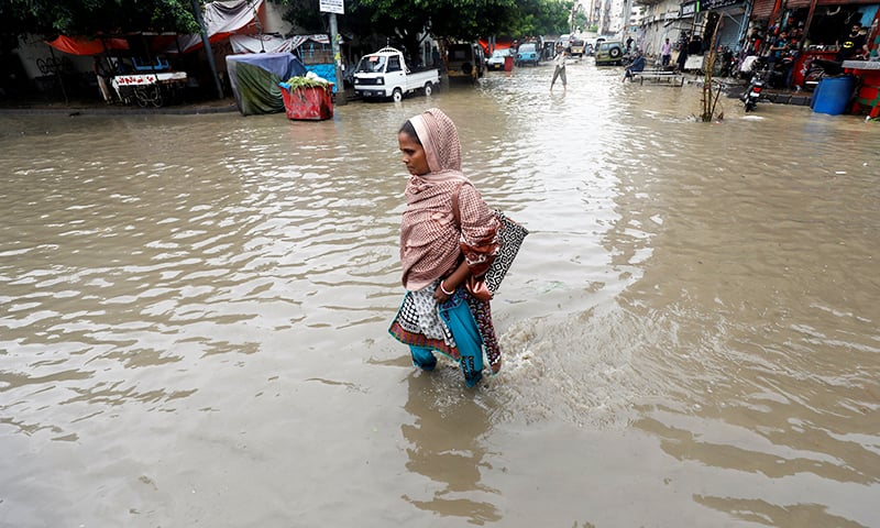 A woman wades through floodwater along a street after heavy rain in Karachi, Pakistan August 11, 2019. REUTERS/Akhtar Soomro