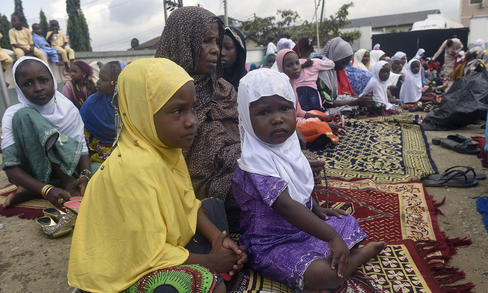 نائیجیریا میں اپنی والدہ کے ساتھ نمازِ عید ادا کرنے والی 2 معصوم بچیاں—تصویر:اے ایف پی