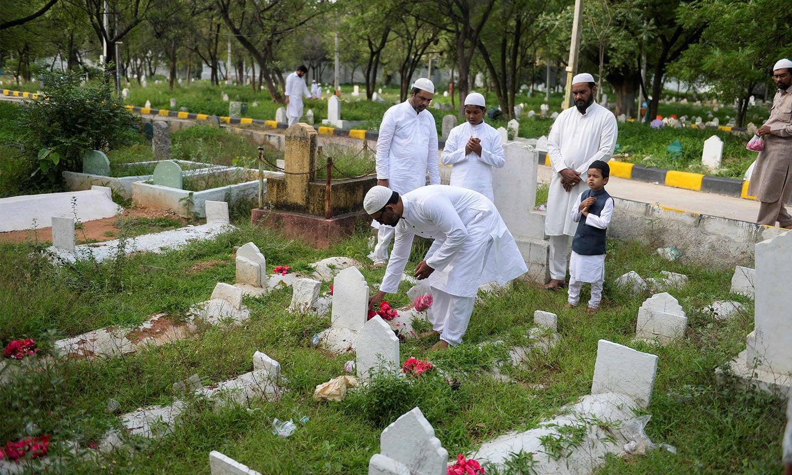 عید کے موقع پر مسلمان اپنے وفات پاجانے والے رشتہ داروں کی قبروں پر فاتحہ پڑھنے قبرستان کا رخ بھی کرتے ہیں—تصویر:اے ایف پی