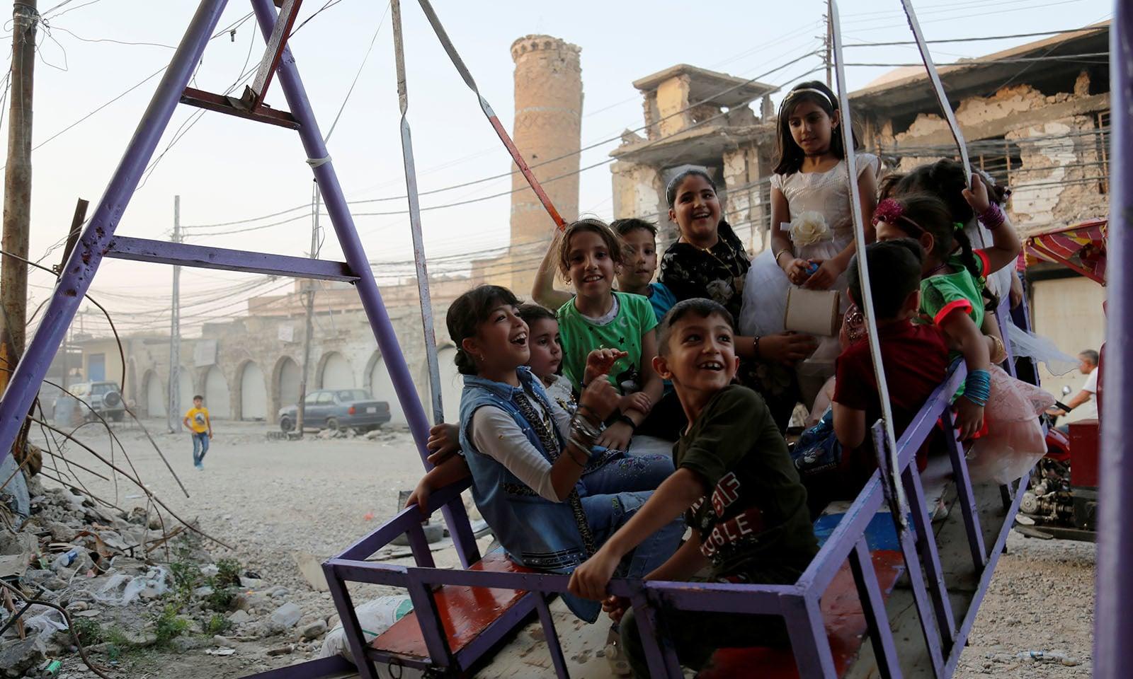 شام میں بچے عید کے موقع پر جھولوں سے لطف اندوز ہوتے ہوئے—تصویر:اے ایف پی
