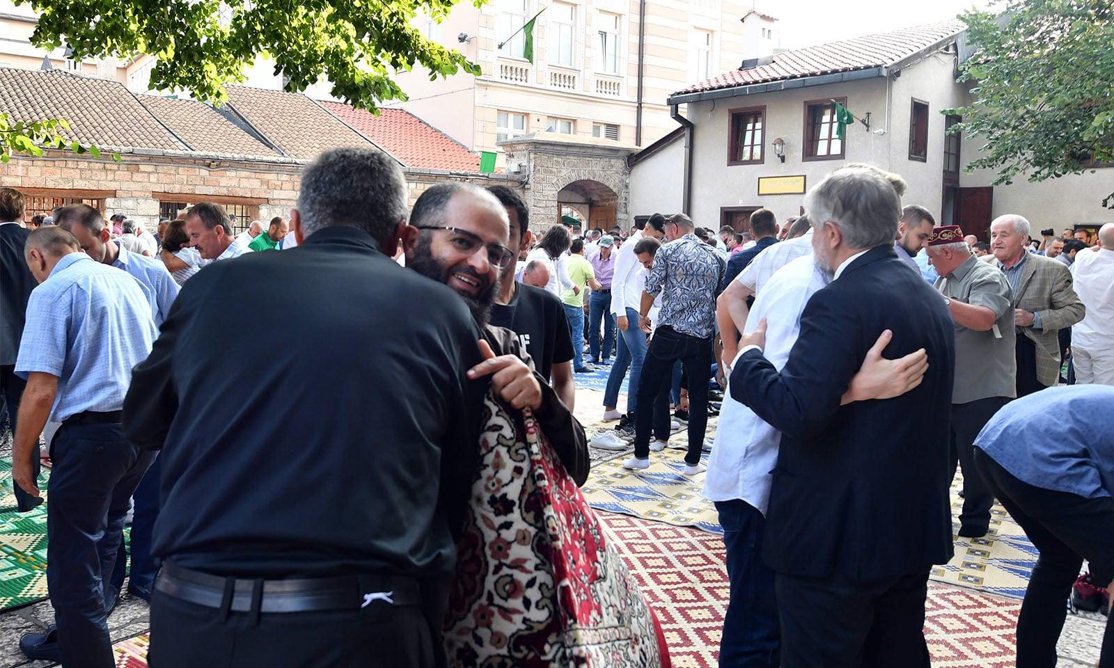 بوسنیا میں اجتماع عید میں شریک 2 احباب ایک دوسرے سے گلے ملتے ہوئے—تصویر:اے ایف پی