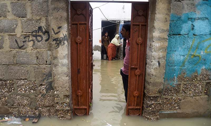 A family shows their flooded house after heavy monsoon rains in Karachi on Aug 11, 2019. — AFP