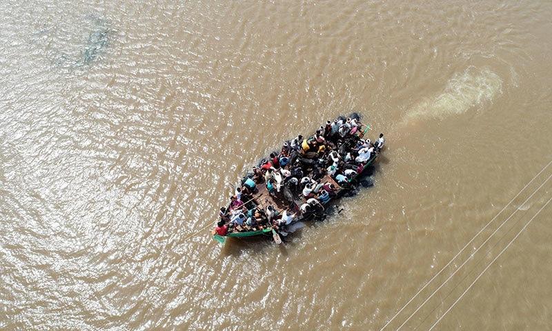بھارتی ریاست کرناٹکا میں لوگوں کو کشتیوں کے ذریعے محفوظ مقام پر منتقل کیا جا رہا ہے— فوٹو: اے ایف پی