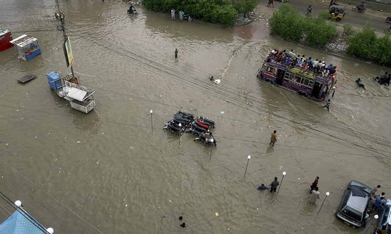 An overloaded bus drives through a flooded road caused by heavy monsoon rains, in Karachi on Aug 11, 2019. — AP