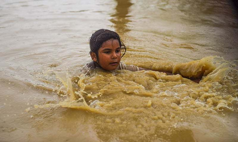 A girl wades through a flooded street after heavy monsoon rains on the outskirts of Karachi on Aug 11, 2019. — AFP