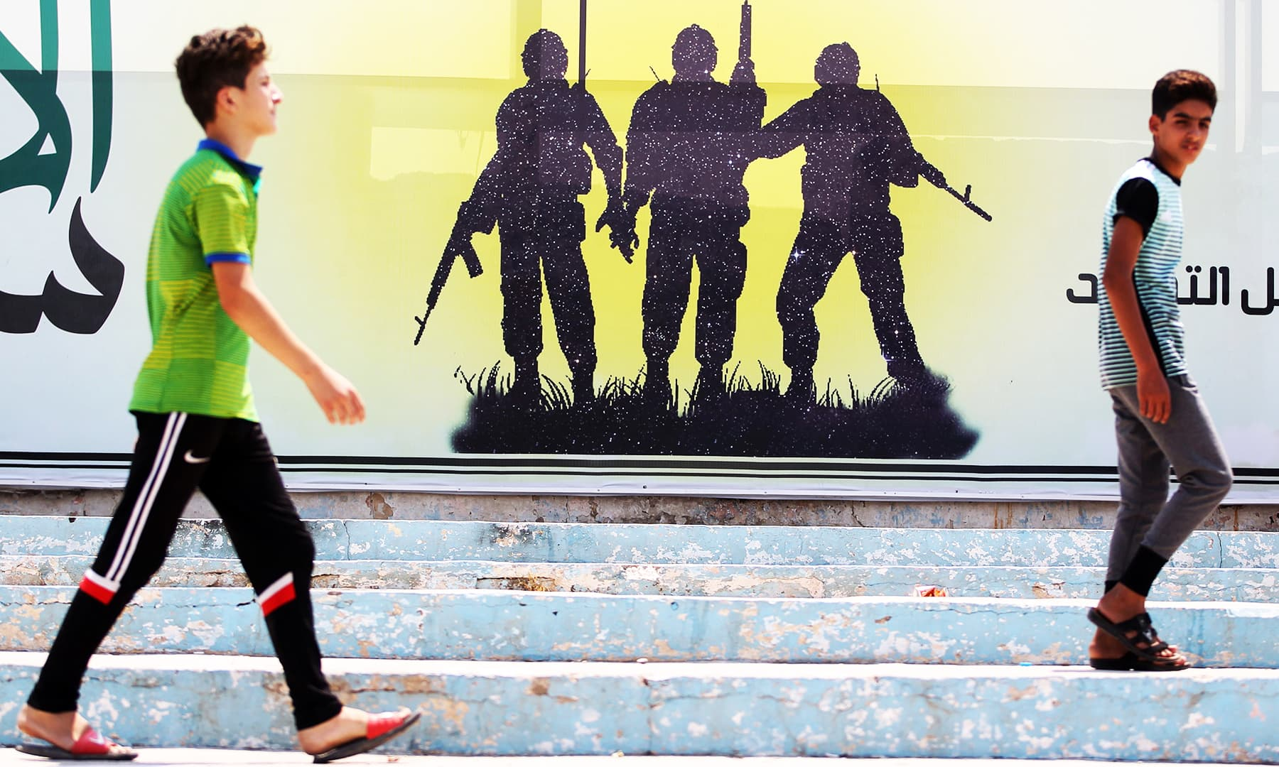 Youths walk past a banner depicting a silhouette of fighters with assault rifles in the Iraqi capital Baghdad's eastern suburb of Sadr City. — AFP
