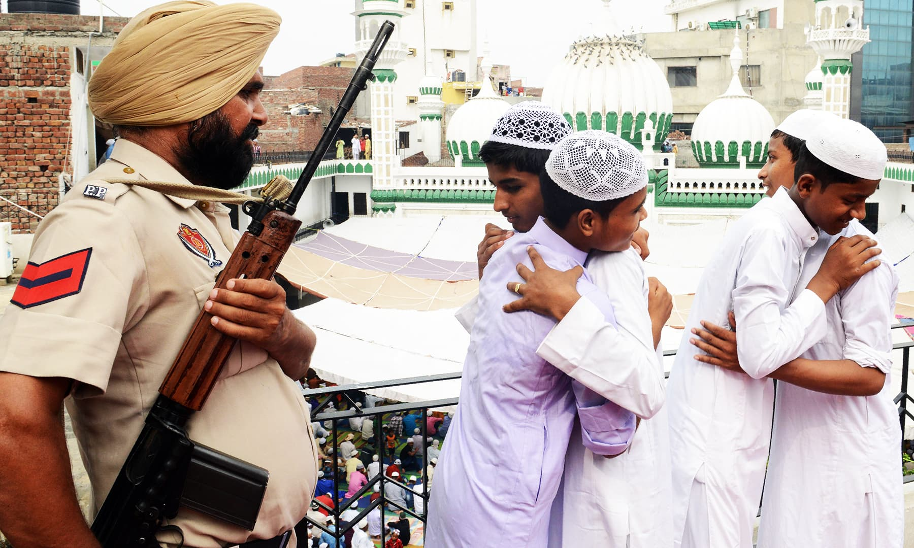 An Indian policeman watches young Muslims greet each other after prayers at the Khairuddin Mosque in Amritsar AFP