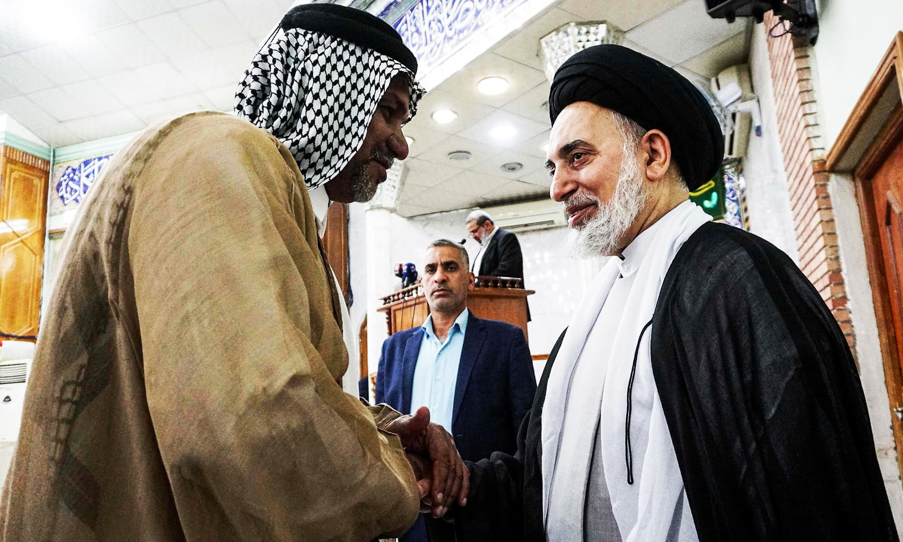 A man shakes hands with a Shia cleric while at a mosque for Eidul Azha prayers, in the central Iraqi shrine city of Najaf south of the capital on Monday. — AFP