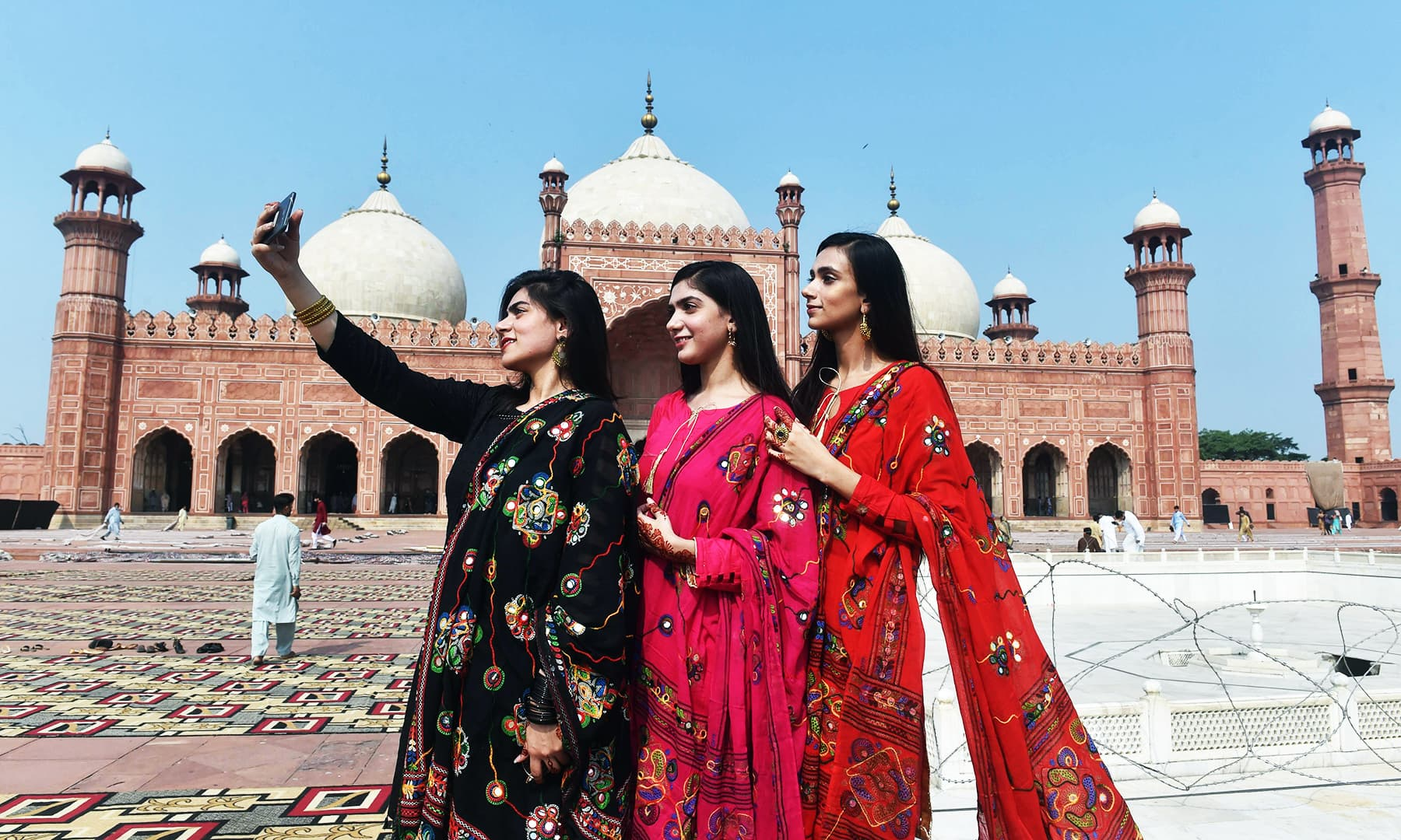 Muslim women take selfie pictures after offering Eidul Azha prayers at the Badshahi Mosque in Lahore. — AFP