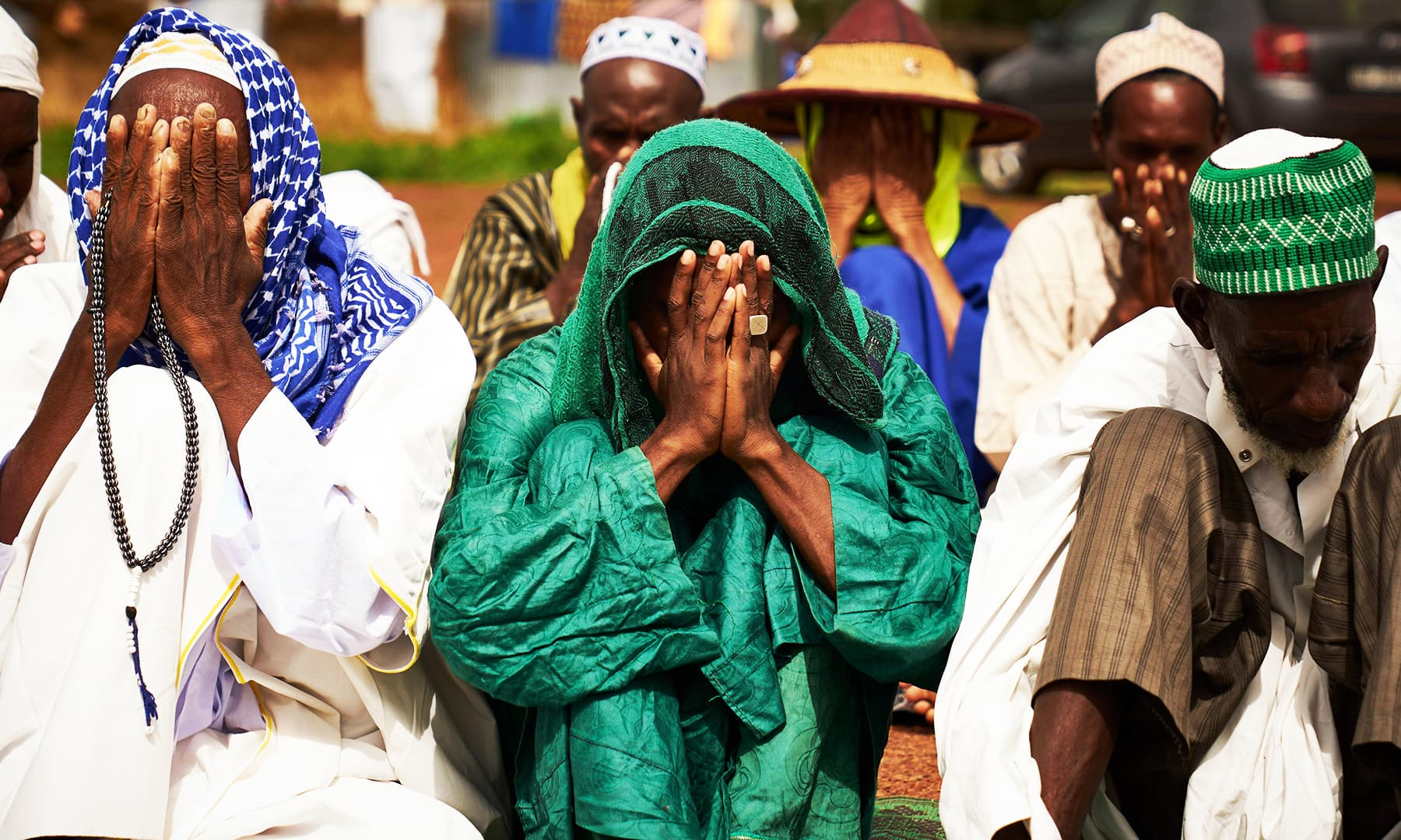 Fulani displaced men cover their faces as they pray during the Eidul Azha in a refugee camp in Bamako on Sunday. — AFP