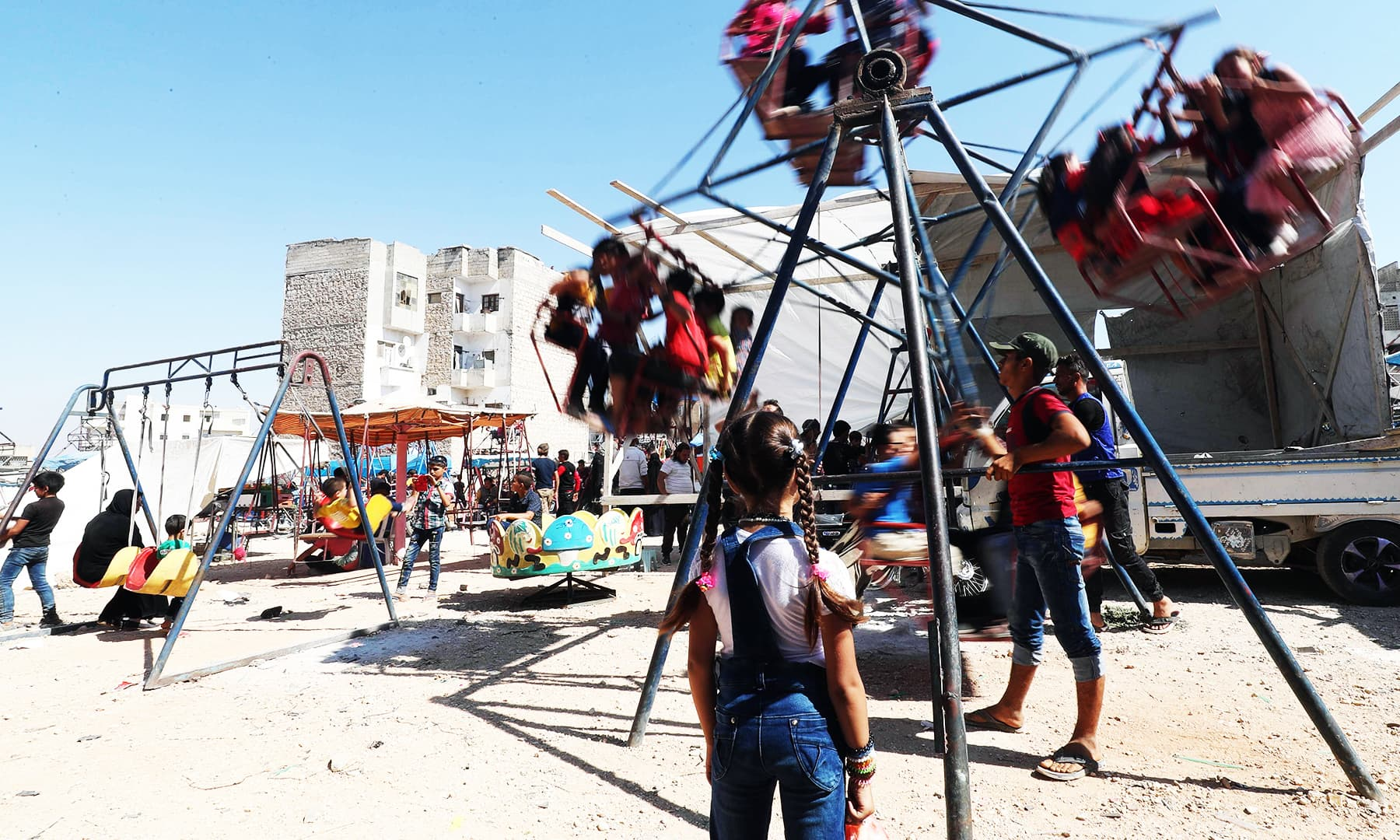 Syrian children sit in rides on the first day of Eidul Azha in the rebel-held city of Idlib in northwestern Syria. — AFP