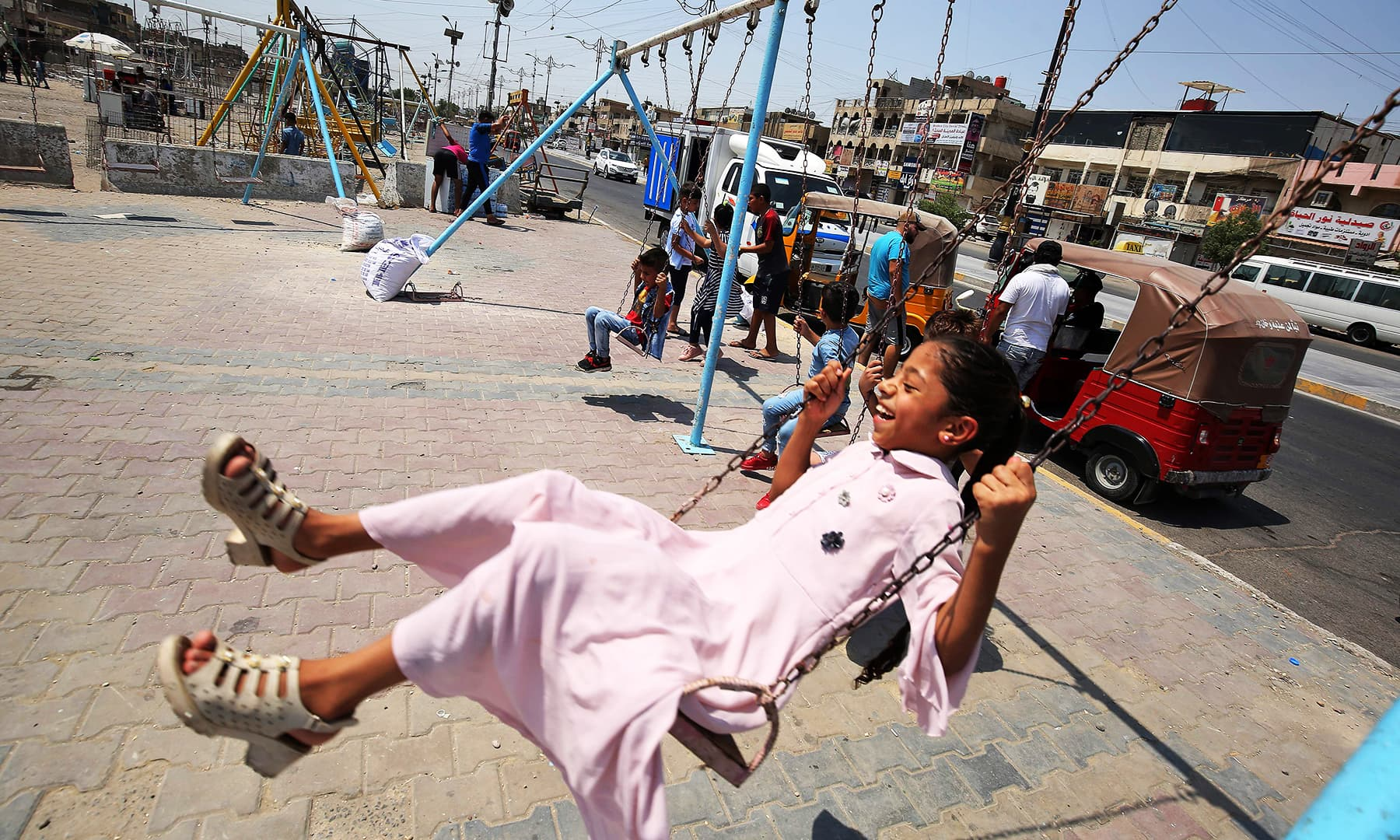A girl rides on a swing in the Iraqi capital Baghdad's eastern suburb of Sadr City. — AFP