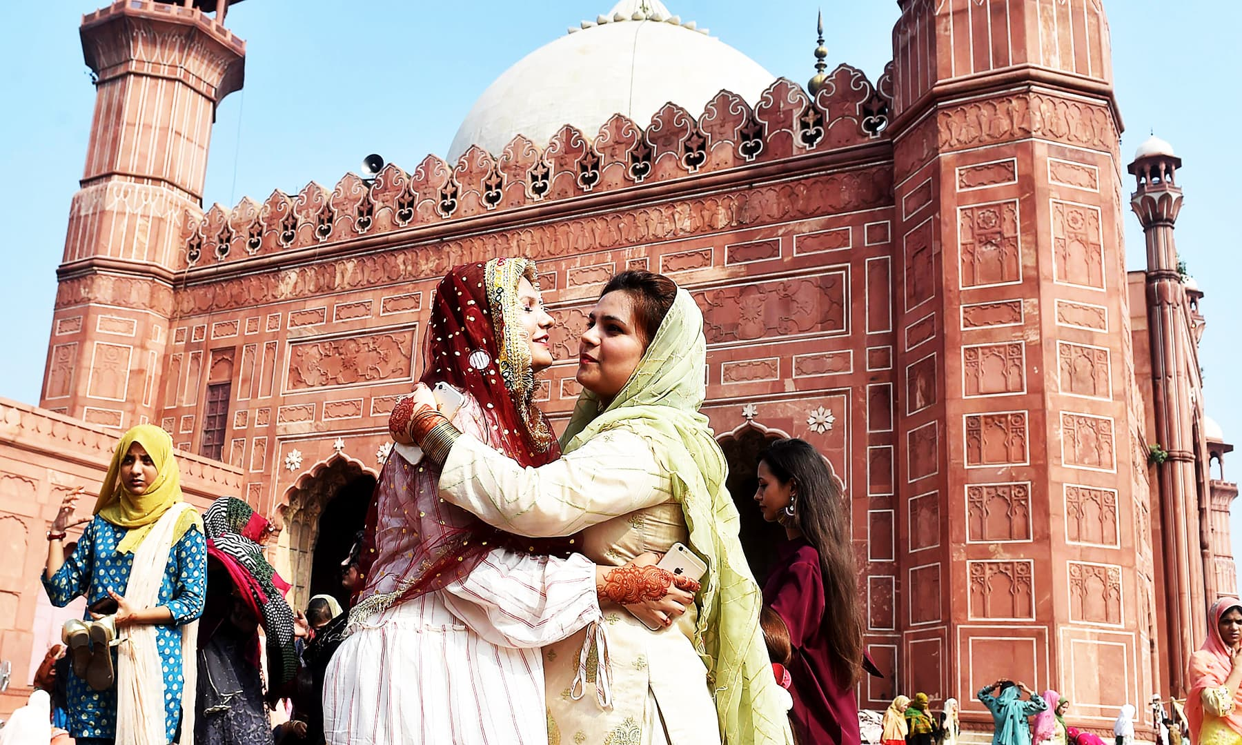 Muslim women exchange Eid greeting after offering Eidul Azha prayers at the Badshahi Mosque in Lahore. — AFP