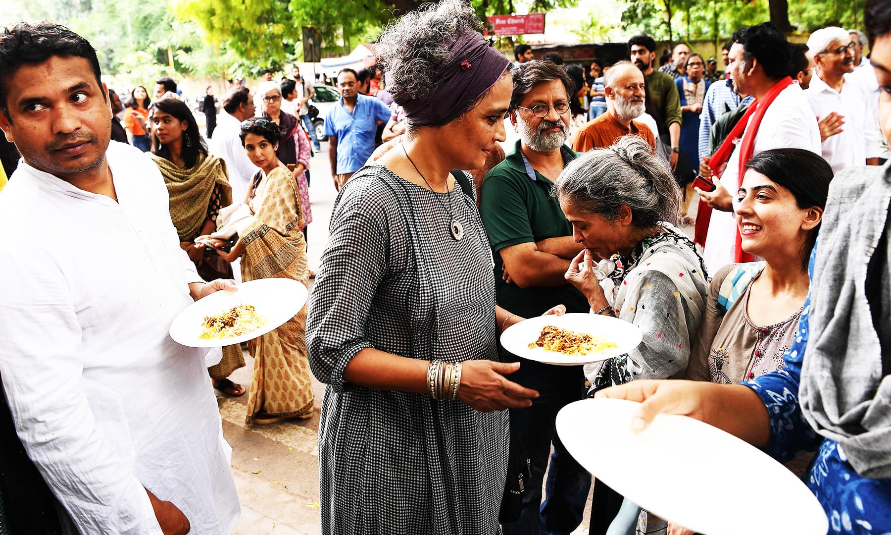 Arundhati Roy (C) takes food with Kashmiri youth during a gathering to celebrate Eidul Azha in New Delhi on August 12, 2019. — AFP