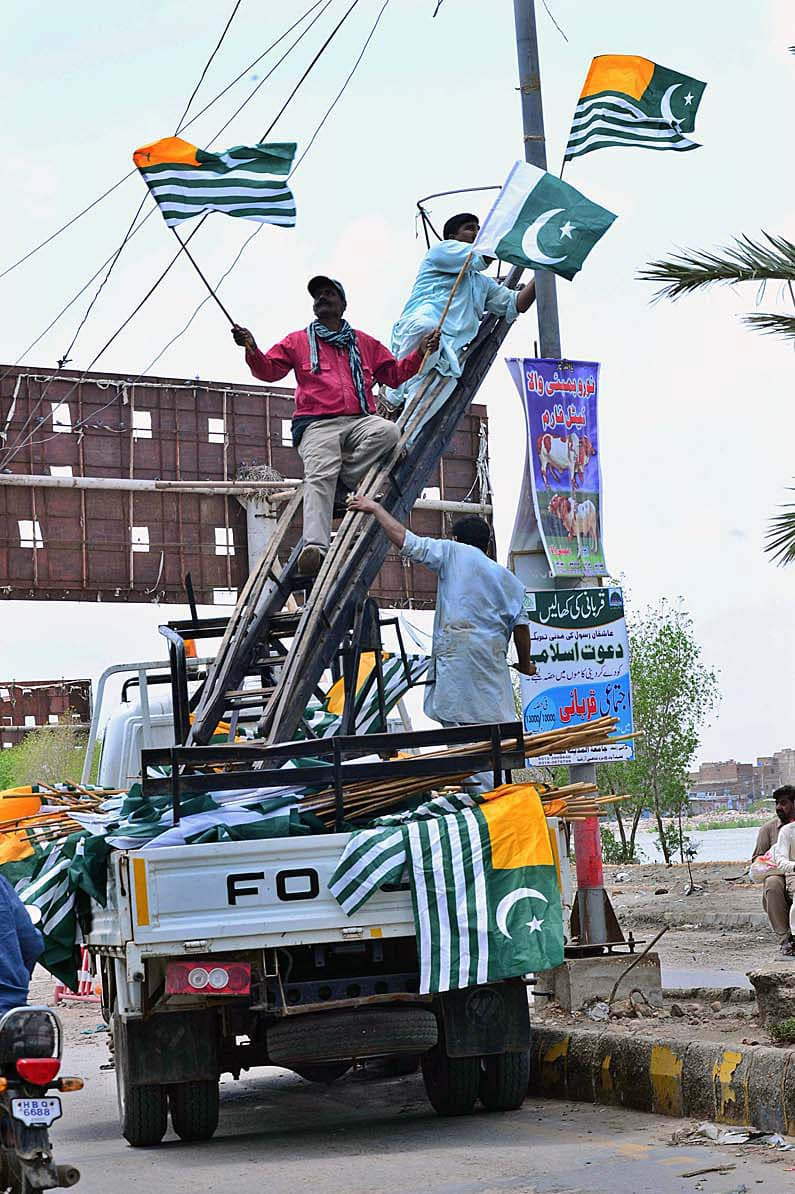 Municipal workers busy installing national & Kashmiri flags on the electric pole at Hilltop Road as the nation prepares to celebrate Independence Day. — APP
