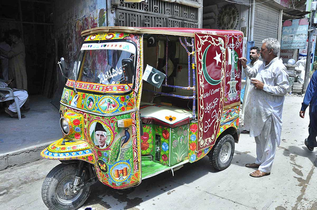 A painter in Rawalpindi decorating an auto rickshaw in connection with Independence Day celebrations. — APP