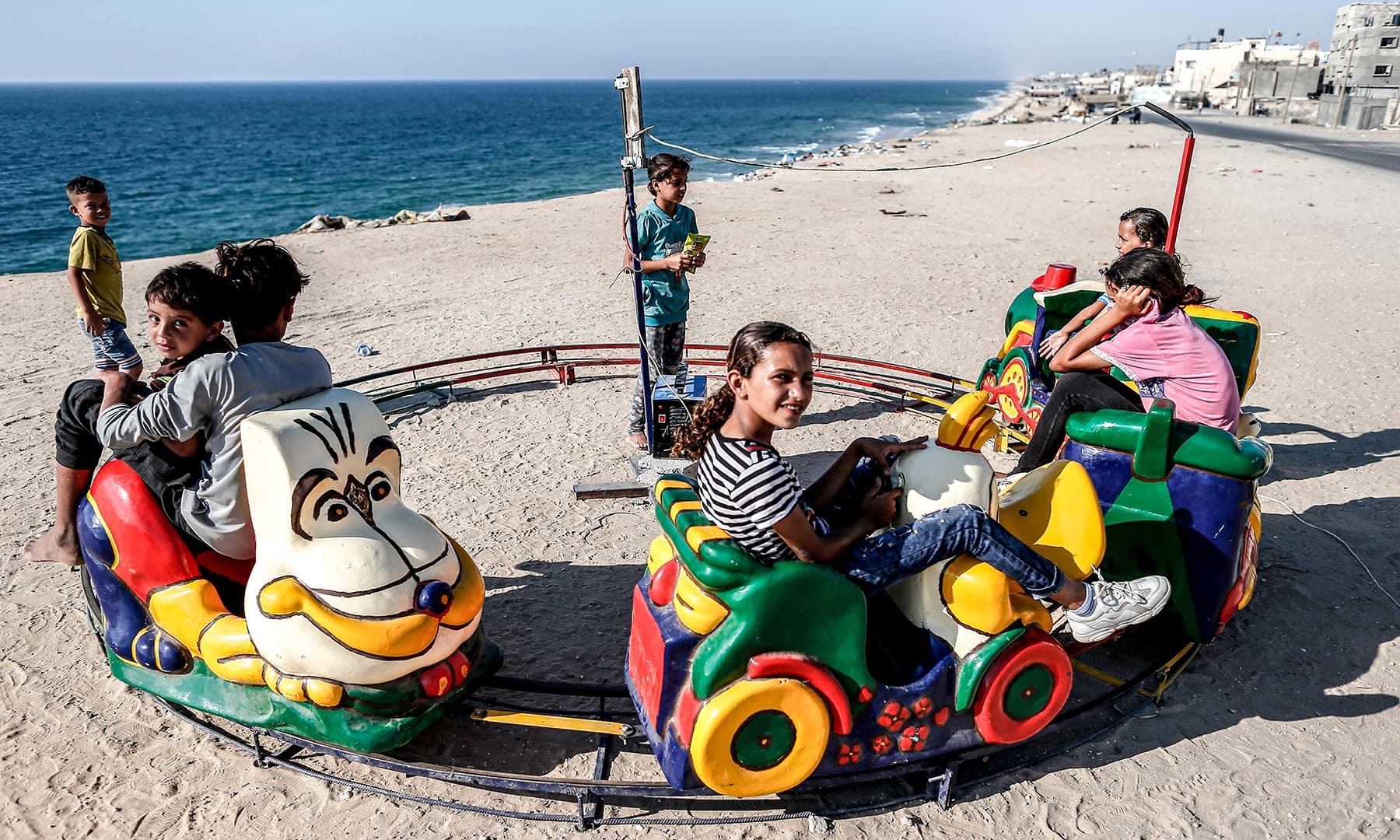 Palestinian children ride on a toy train overlooking the Mediterranean, while celebrating during the third day of Eidul Azha in the Deir al-Balah refugee camp in the central Gaza Strip on Tuesday. — AFP