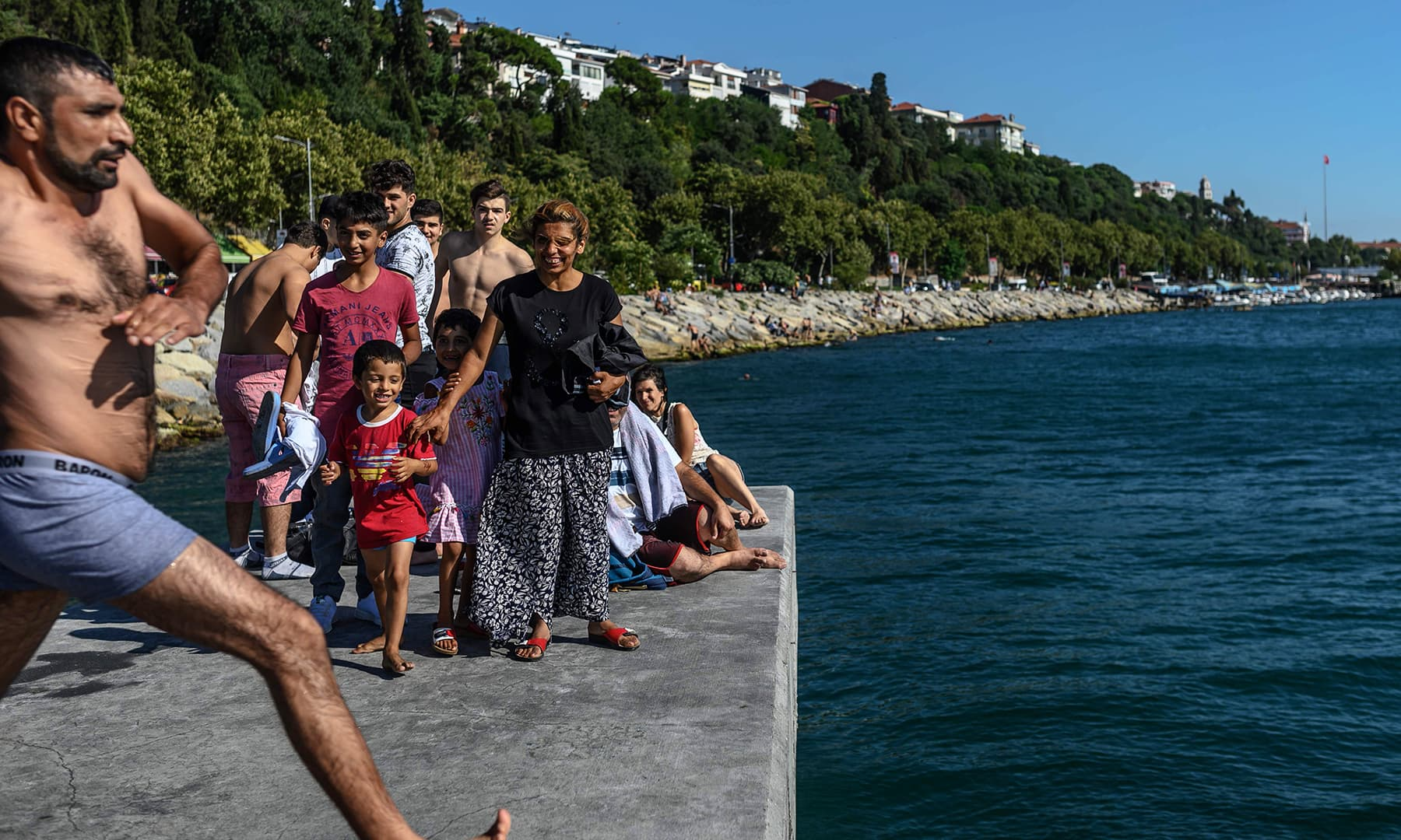 A Turkish woman watches her husband with her children as he jumps into the Bosphorus during the Eidul Azha festival on Monday, in Istanbul. — AFP