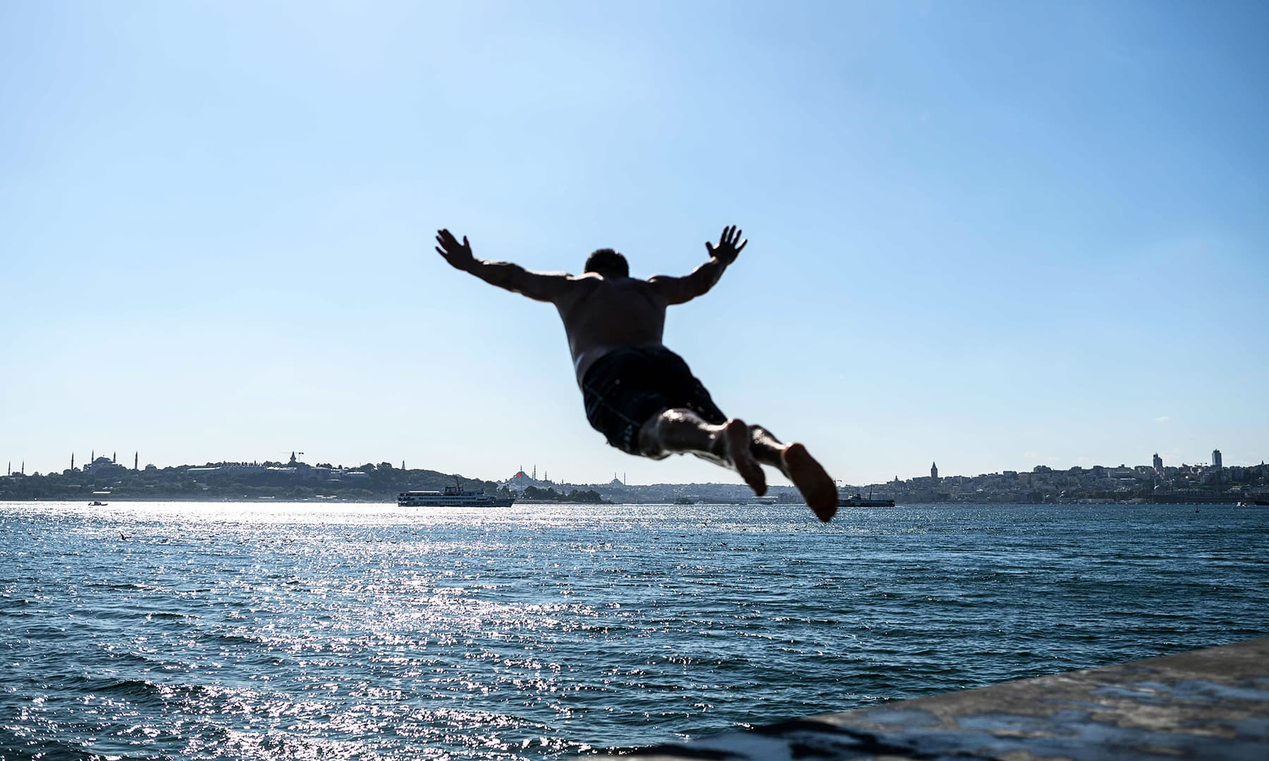 A man dives into the Bosphorus during the festival of Eidul Azha on Monday, in Istanbul. — AFP