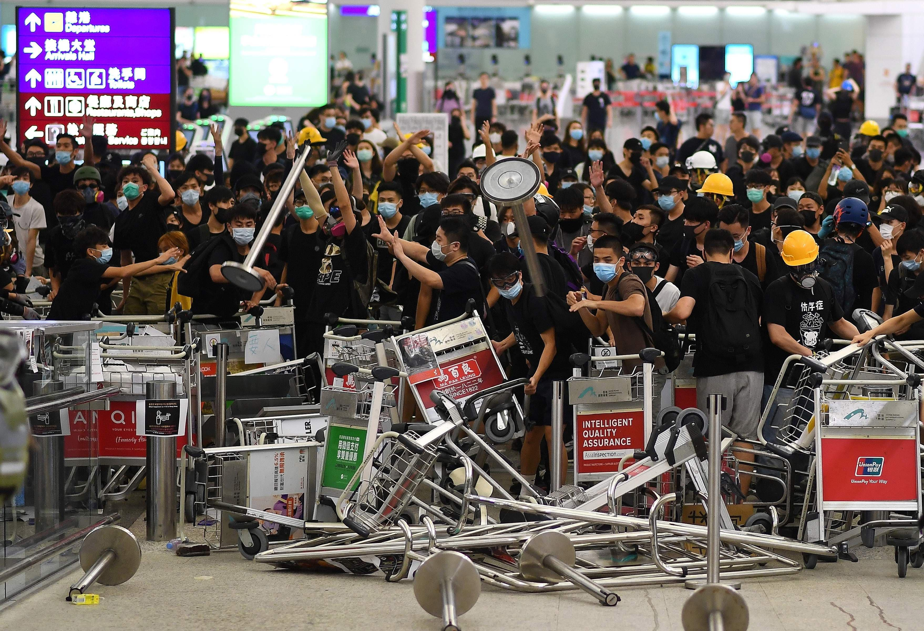 Pro-democracy protestors block the entrance to the airport terminals after a scuffle with police at Hong Kong's international airport on Tuesday. — AFP