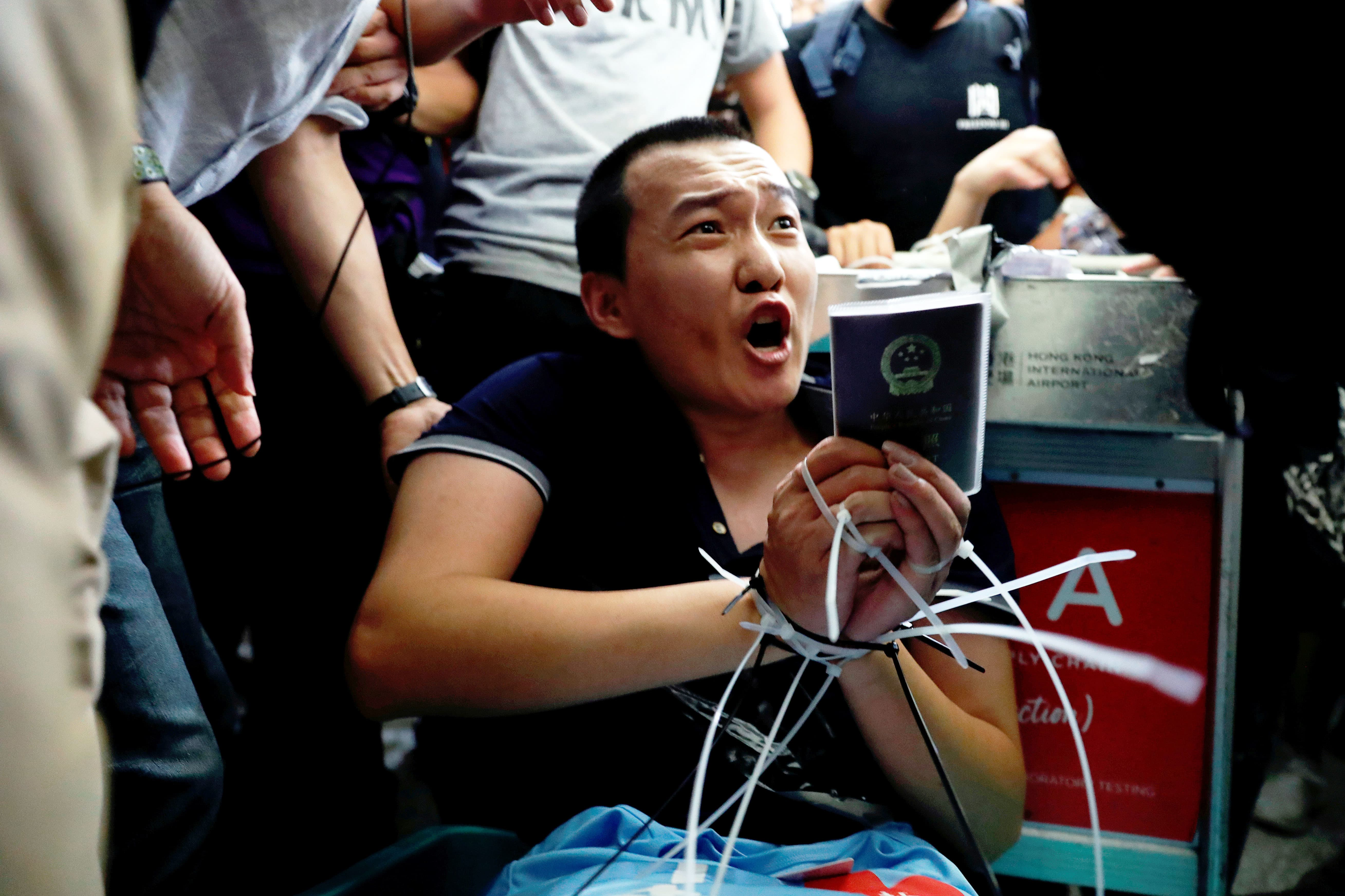 Fu Guohao, reporter of Chinese media Global Times website, is tied by protesters. — Reuters