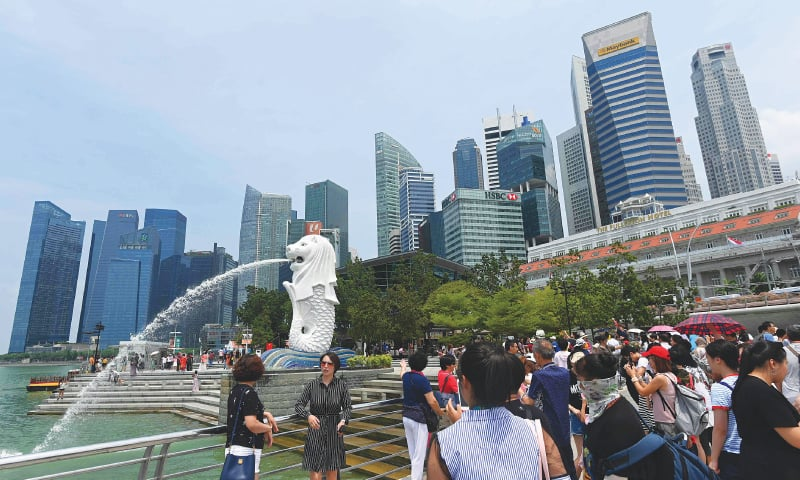 Visitors take photographs at the Merlion park in Singapore on Tuesday. — AFP