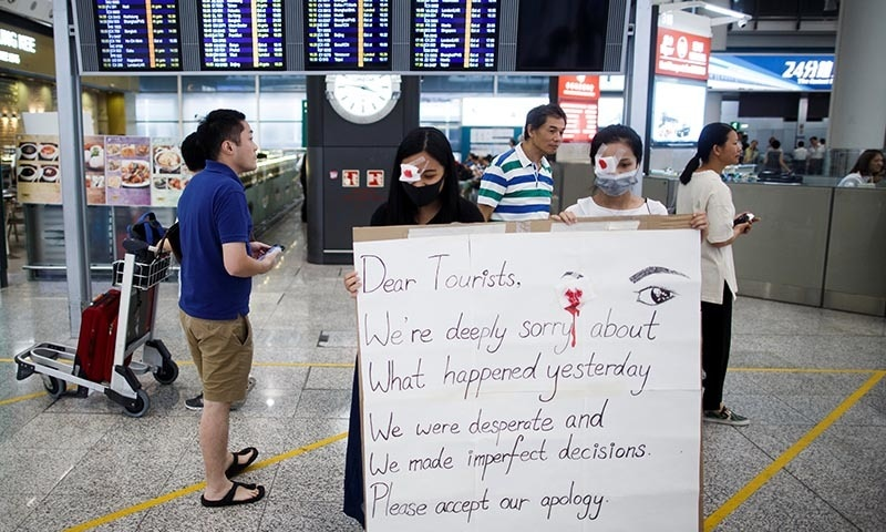 Anti-government demonstrators apologise for yesterday's clashes with police at the airport in Hong Kong China on August 14. — Reuters