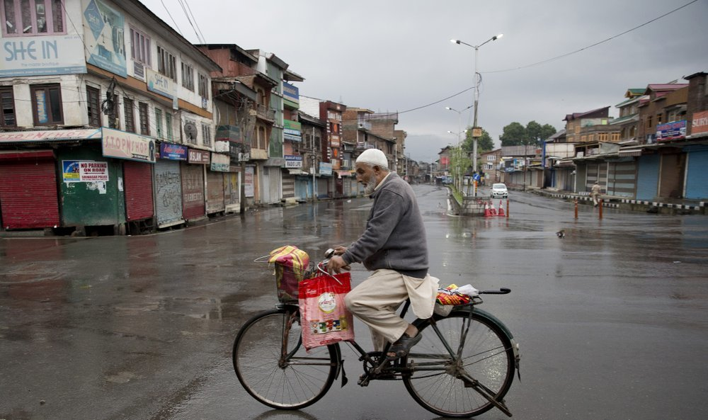 A Kashmiri man rides a bicycle through a deserted street during security lockdown in Srinagar on Wednesday. ─ AP