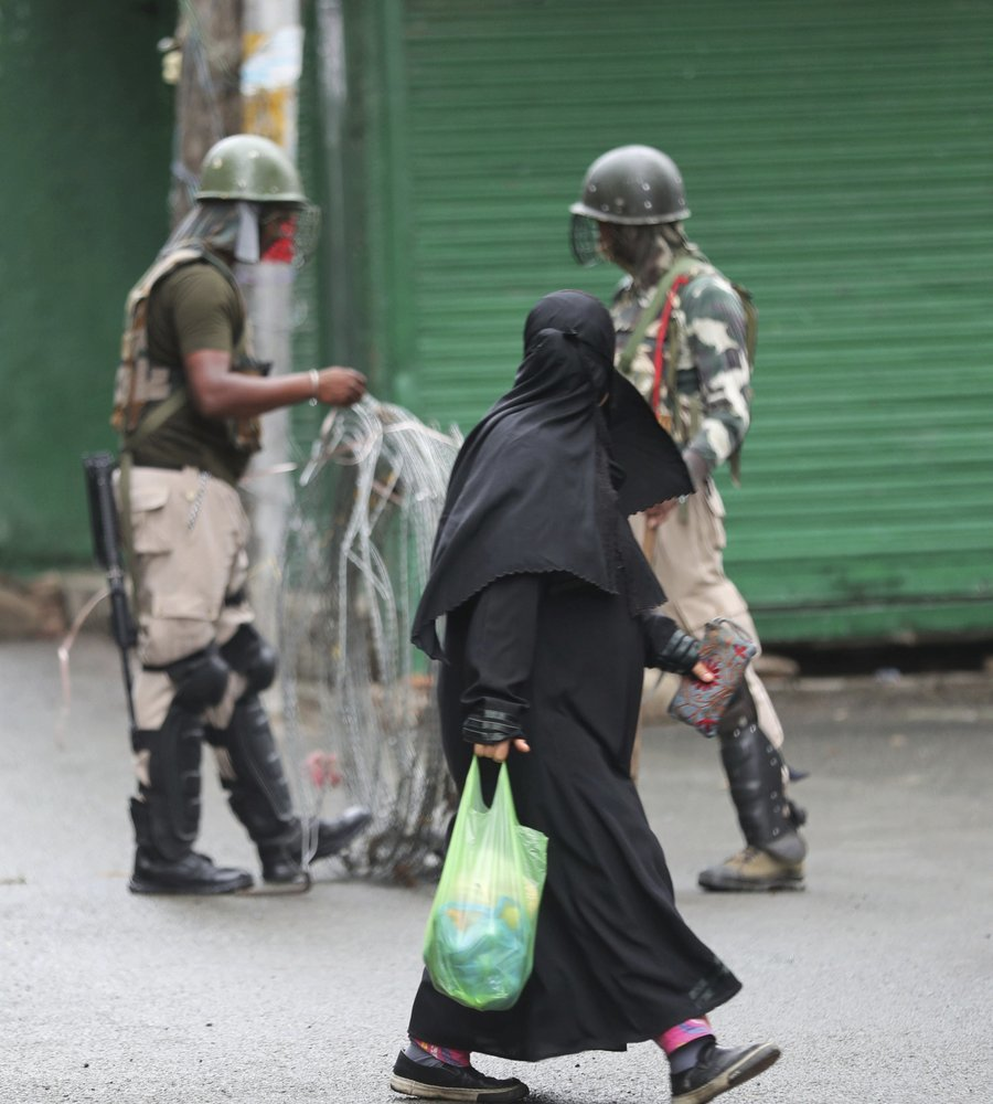 A Kashmiri woman walks past Indian paramilitary soldiers closing off a street with barbwire in Srinagar on August 10. ─ AP