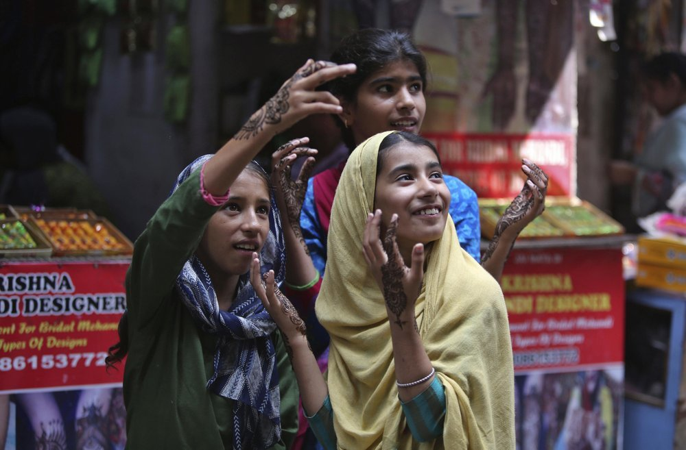 Kashmiri girls gesture after getting henna decorations on their hands on the eve of Eidul Azha in Jammu on August 11. ─ AP