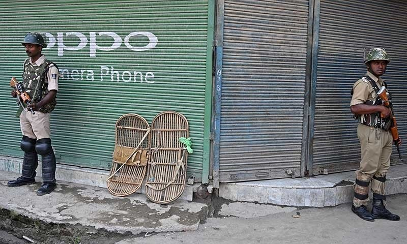 Indian paramilitary troopers stand next to shuttered stores in Srinagar in occupied Kashmir on August 2. — AFP/File