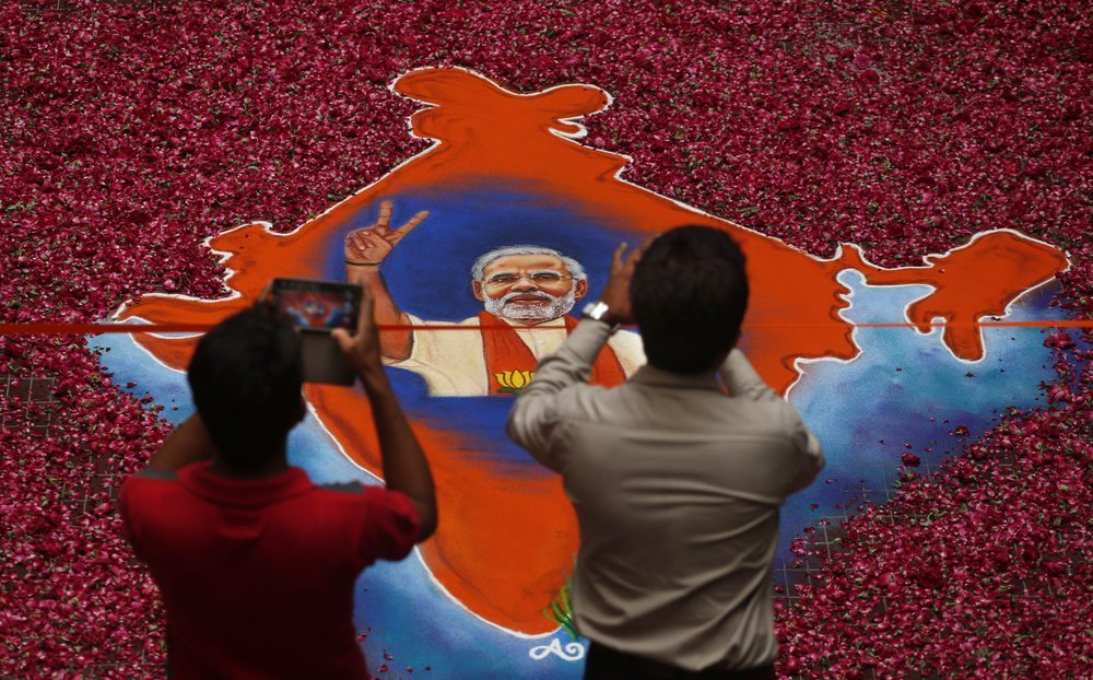 In this 2014 file photo, Indians take photographs of a portrait of Bharatiya Janata Party (BJP) leader Narendra Modi, with an outline of the India map made with colored powder and surrounded by rose petals, in Gandhinagar, Gujarat state, India. — AP