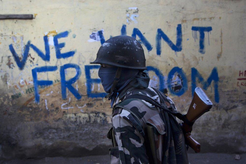 In this 2016 file photo, an Indian paramilitary soldier walks past graffiti on a wall in Srinagar. ─ AP
