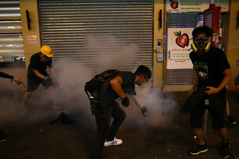 Pro-democracy protestors pour water on tear-gas shells fired by police in the Sham Shui Po area of Hong Kong. ─ AFP