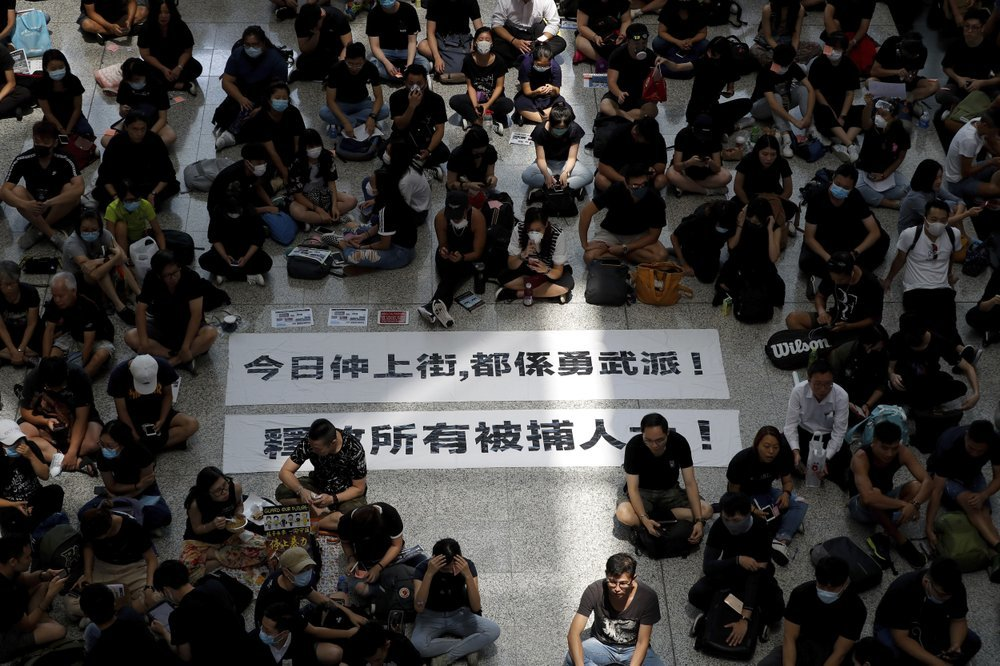 "Protesters surround banners that read: ""Those charge to the street on today is brave!,"" top, and ""Release all the detainees!"" during a sit-in rally at the arrival hall of the Hong Kong International airport on Monday. ─ AP"