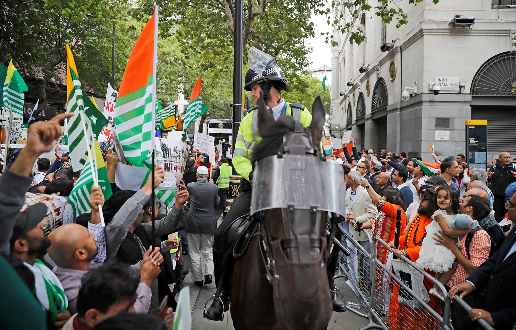 A British mounted police officer sits on his horse between pro-Pakistan (L) and pro-India (R) demonstrators as they protest outside of the Indian High Commision in central London on Thursday. — Reuters