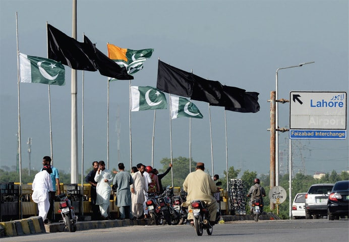 Black flags flutter along with national and Kashmir flags on Faizabad Bridge on Thursday. — Photo by Mohammad Asim