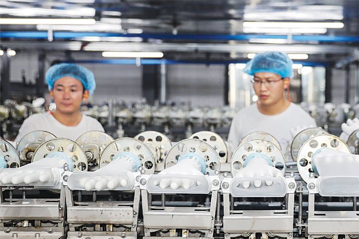 HUAIBEI: employees working on a medical glove production line at a factory in China's eastern Anhui province on Thursday.—AFP