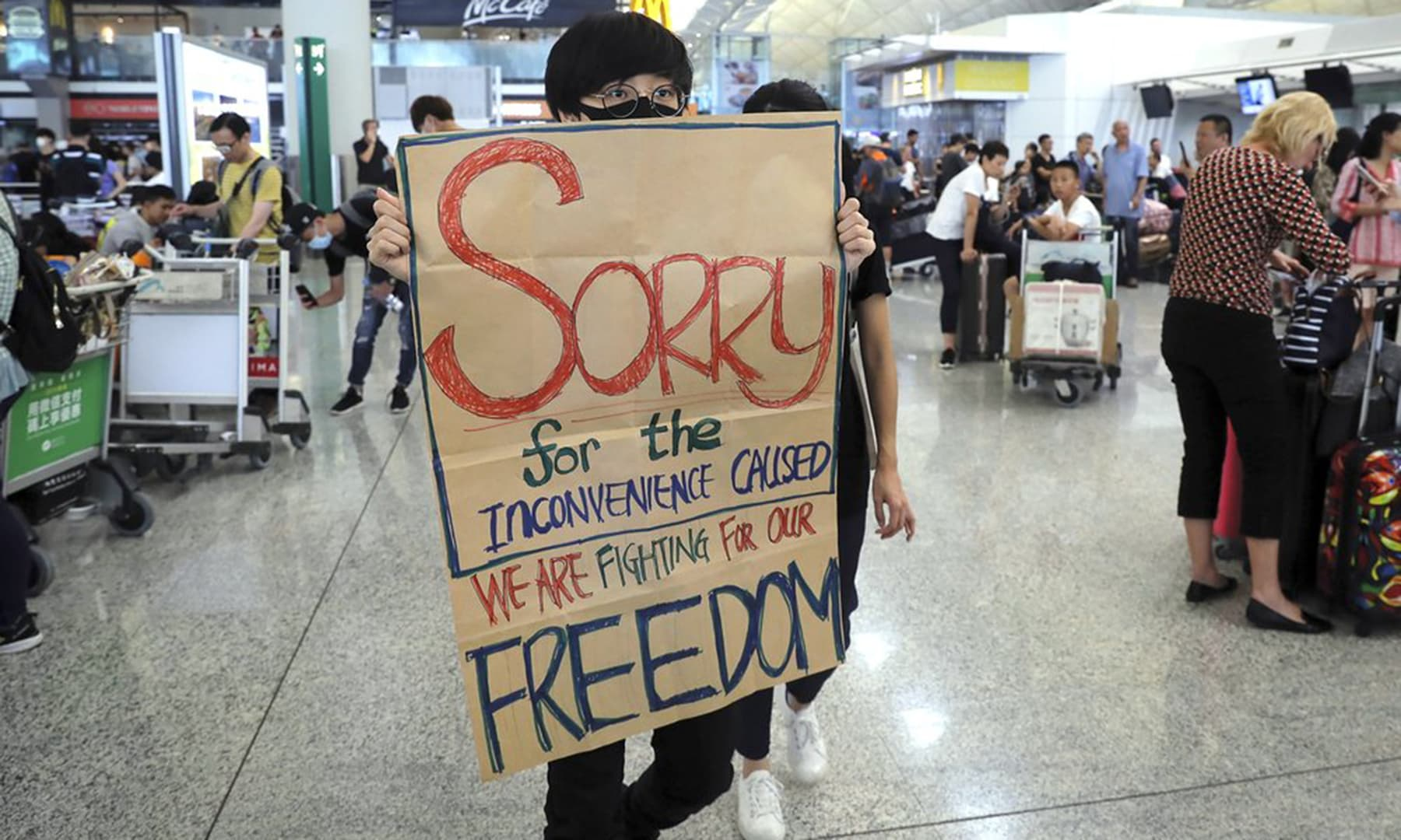 A protester shows a placard to stranded travellers during a demonstration at the Airport in Hong Kong on Aug 13, 2019. — AP