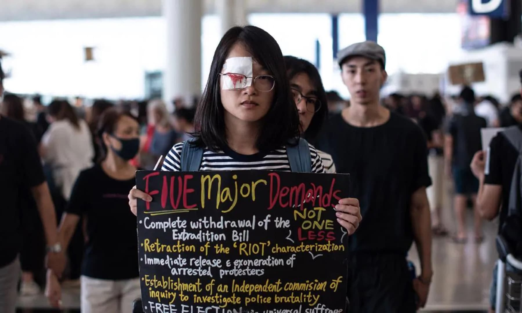 A pro-democracy protester holds a placard during another demonstration at Hong Kong's international airport. — AFP
